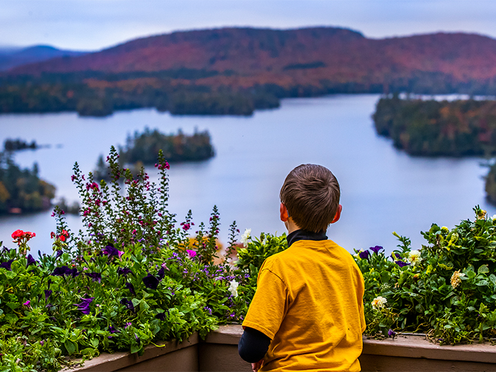 A boy looks out at the view of Blue Mountain Lake and the changing foliage from the deck of the Lake View Cafe.