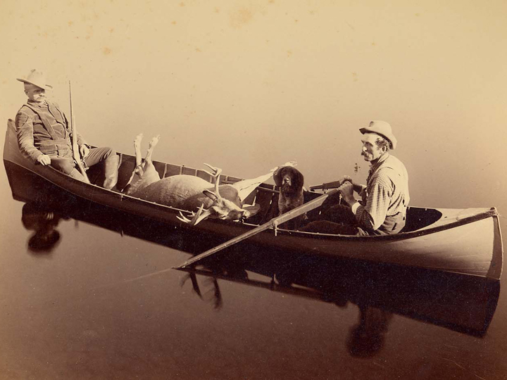 Seneca Ray Stoddard, Ed. McAlpin – later General, c. 1890 The hunter McAlphin sits in the stern of the guideboat. His guide, Jack Richards, sits in the bow next to a hunting dog. (P019986)