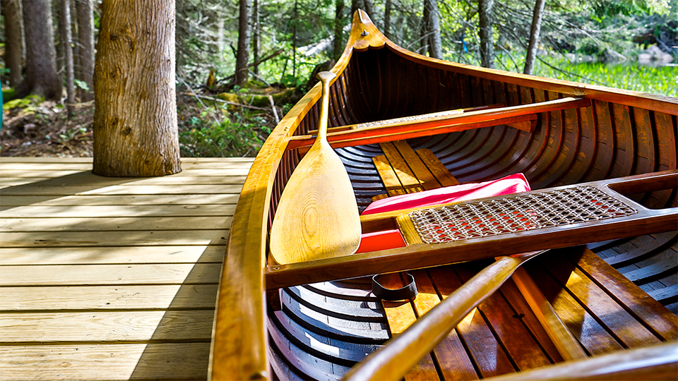 A close up a beautifully restored wooden canoe, available to use on Minnow Pond.
