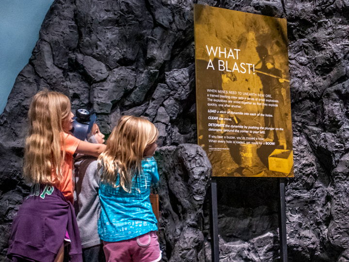 A group of three children participating in the interactive exhibition about mining in the Adirondacks.