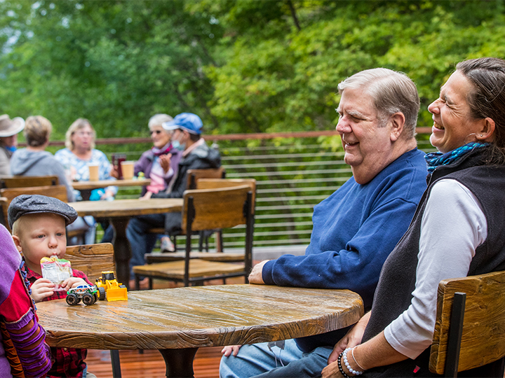 A family enjoying each others company talking and laughing on the deck of the Lake View Cafe at the Adirondack Experience.