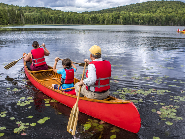 A family of 3 paddling out onto Minnow Pond in a vintage canoe from the ADKX Boathouse.