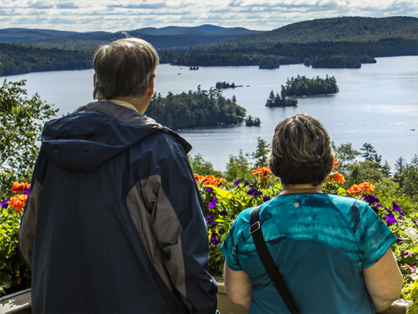 A couple taking in the view of Blue Mountain Lake from the deck of the Lake View Cafe at the Adirondack Experience.