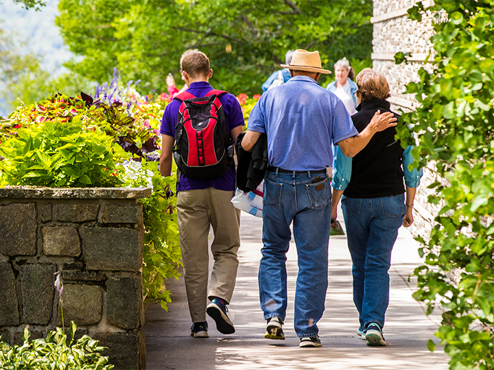 An elderly couple and young man walk a path with beautiful flowers blooming.