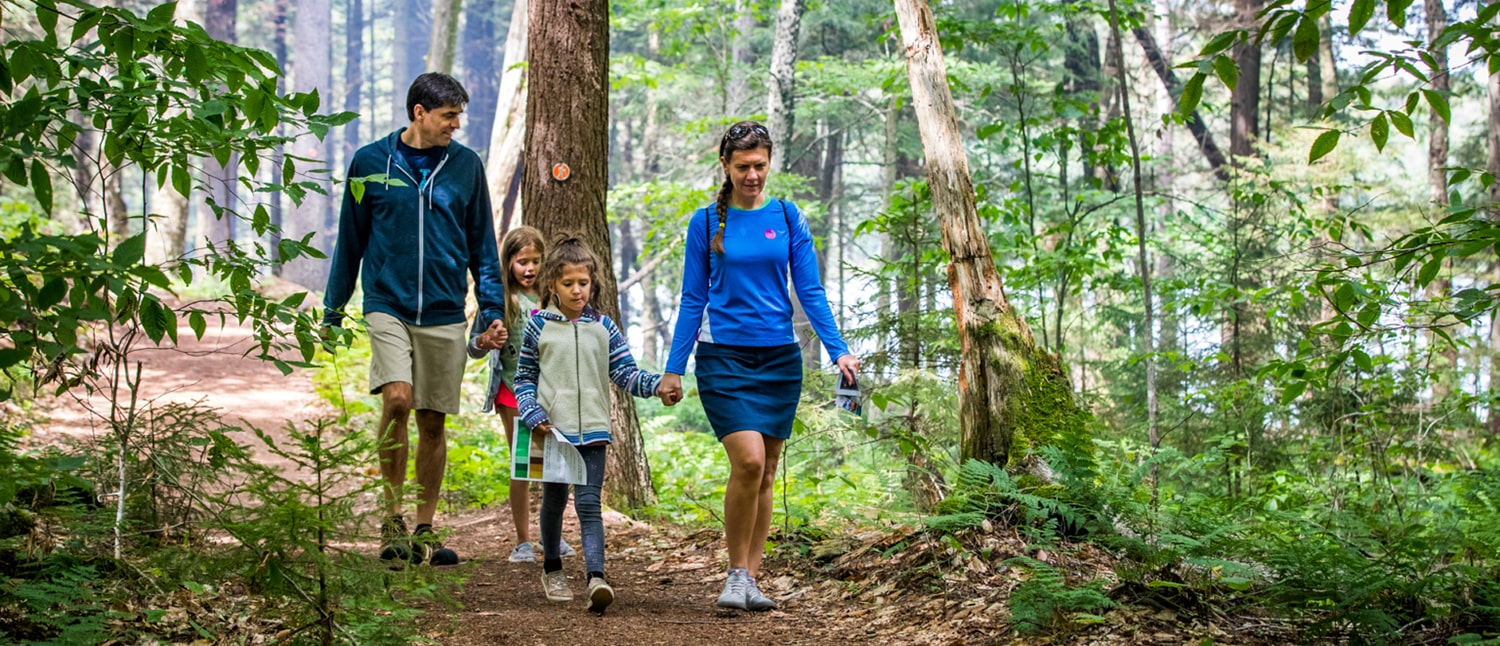 A family of four hiking the Minnow Pond trail to the Boathouse.
